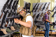 Male customers try on ammunition with weapon