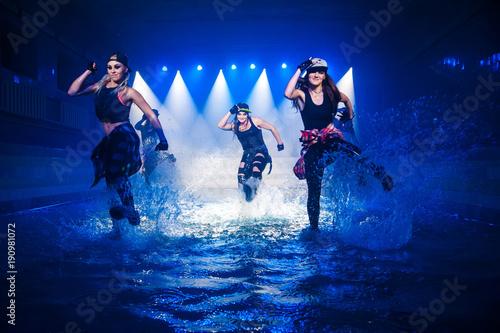 Zdjęcie XXL Występ na wodzie grupy tanecznej na tle światła klubowego.