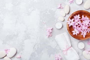 Aromatherapy, beauty, spa background with massage pebble, perfumed flowers water and candles on stone table top view. Relaxation and zen like concept. Flat lay.