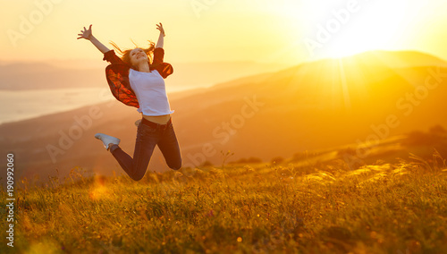 Fotografia  Happy woman jumping and enjoying life  at sunset in mountains