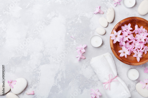 fototapeta na szkło Aromatherapy, beauty, spa background with massage pebble, perfumed flowers water and candles on stone table top view. Relaxation and zen like concept. Flat lay.