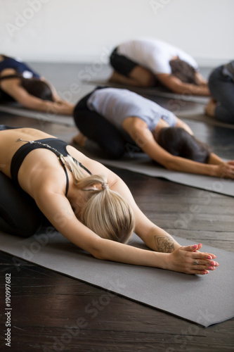 Poster Ecole de Yoga Group of young sporty people practicing yoga lesson with instructor, stretching in Child exercise on mat, Balasana pose, working out, indoor close up, students training in club, studio