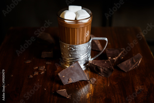 An underexposed horizontal image of hot chocolate in a glass in a metal glass-holder, decorated with marshmallows and pieces of dark chocolate on a wooden table. Selective focus.