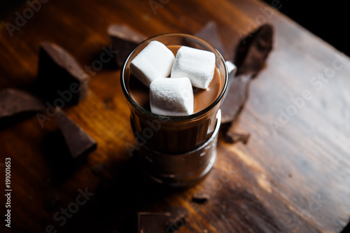 Spoed Foto op Canvas Chocolade An underexposed horizontal image of hot chocolate in a glass in a metal glass-holder, decorated with marshmallows and pieces of dark chocolate on a wooden table. Selective focus.