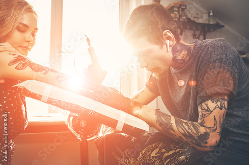 Photo A young guy, beats a tattoo on the hand of the girl in a tattoo parlor, rotary t