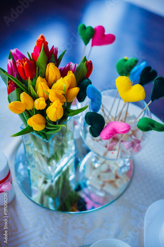 Fototapety, obrazy: Glass vase with bouquet of red, yellow and pink tulips stands on the table with candles and bowls with sweets
