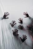 rozmyte straszne sylwetki ludzkich rąk dotykając matowego szkła - 191017240