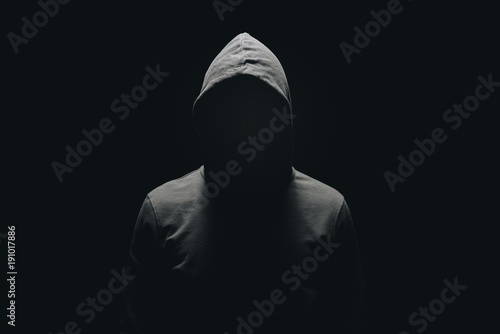 Fotomural  faceless man in hoodie standing isolated on black