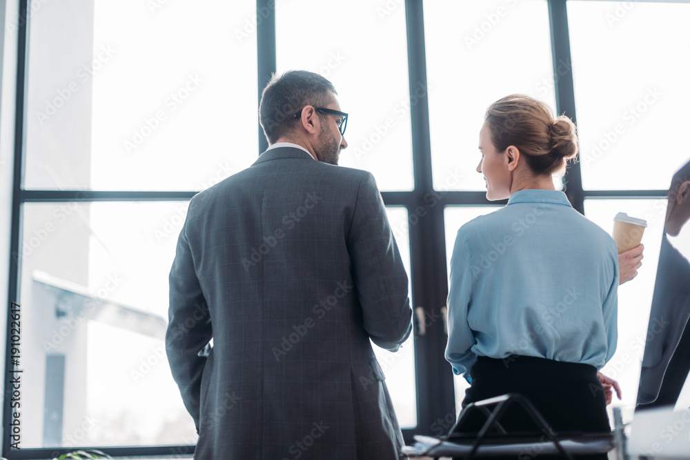 Fototapeta rear view of businesspeople having conversation at office and drinking coffee