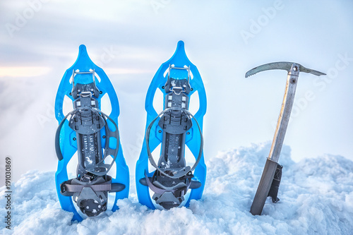 Foto op Plexiglas Alpinisme Touristic Climbing equipment Snow shoes and ice ax at the background of endless clouds on the mountain summit. Snowy winter scene.