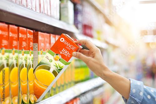 Woman hand choosing to buy orange juice on shelves in supermarket