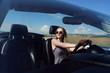 Girl driving a convertible car in a summer poppy field