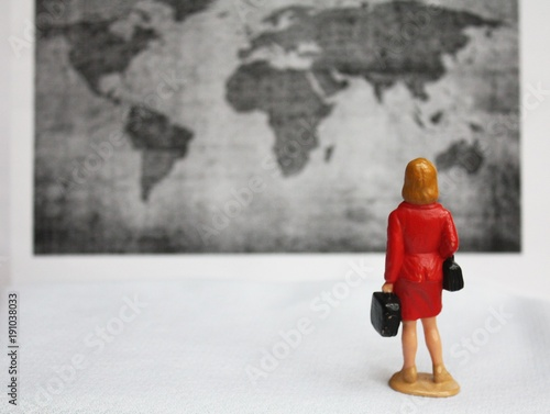 Miniature woman from behind on a business trip. Traveling around the world concept. Blurred black and white map of the worl background.