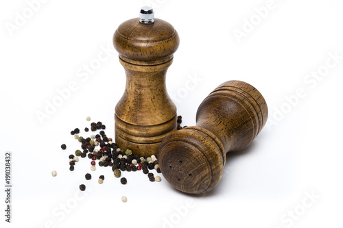 Fotografía  Wooden salt shaker and pepper mill surrounded by diverse peppercorns on white background