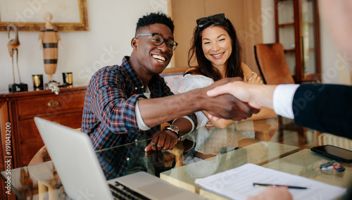 Photo  Couple handshaking realtor after signing contract