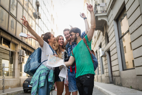 Young happy tourists sightseeing in city Wallpaper Mural