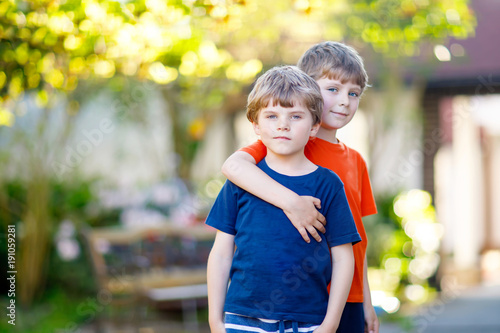 two little active school kids boys twins and siblings hugging on