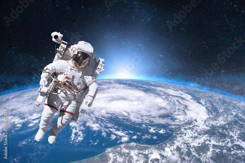 Fotografie, Obraz Astronaut in outer space on background of the Earth