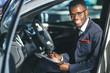 Handsome young african car salesman standing at the dealership holding a tablet