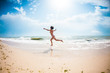 A girl is jumping on the beach.