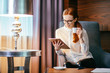 Redhead young woman wearing glasses drinking coffee and reading her touchscreen tablet while standing in office