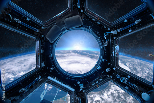 View from a porthole of space station on the Earth background. Elements of this image furnished by NASA.