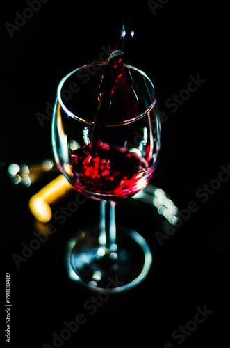 pouring red wine in a glass, celebration of a moment with a glass of wine, exquisite liquor for gourmets