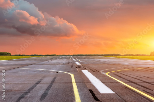 Poster de jardin Aeroport Runway at the airport the horizon at sunset in the center of the sun.
