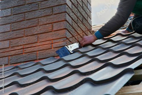 Cuadros en Lienzo Roofer builder worker attach metal sheet to the chimney
