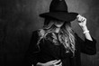 Beautiful young mysterious blond girl in black hat and black jacket on gray background. Eyes are covered with a hat. Manicure - long red nails, nail polish. Fashion, beauty.