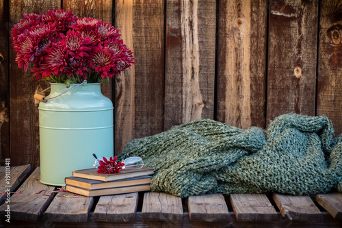 Fotografía  Red mums next to a pair of wire rimmed glasses sitting on antique books and next to a knubby green knitted blanket