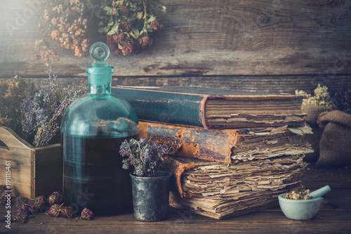 Fotografie, Obraz  Tincture bottles, assortment of dry healthy herbs, old books, mortar, curative drugs