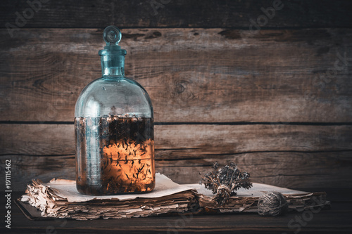 Fototapeta Tincture or potion bottle, old book and bunch of dry healthy herbs. Herbal medicine. Retro styled. obraz