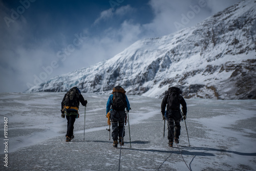 Poster Climbers walking across glacier towards snowy limestone mountains