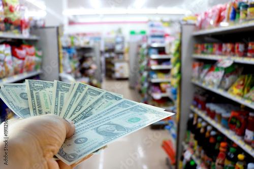 Plakat Ręka trzyma dolary w sklepie. Mężczyzna trzyma dolary dla gotówki w sklepie. Pieniądze na wymianę handlową. Zdjęcie koncepcji finansów i pieniędzy.