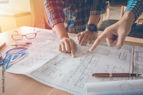 Concept architects, Two asian engineer pointing equipment architects On the desk with a blueprint in the office, Vintage, Sunset light.Selective Focus