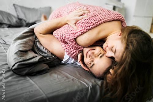 Fotografia  Szczęśliwi potomstwa dobierają się kłaść na łóżku