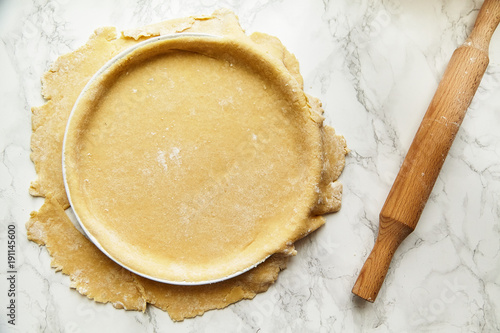 Fotomural Rolling a pastry for baking a pie and pricking it with fork