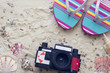 Enjoying vacation mood, beach sneakers and roll film vintage camera on white sand background. Space for a text or product display, top view.
