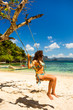 Curly girl on a swing at the beach near Cudugnon Cave, Palawan, Philippines