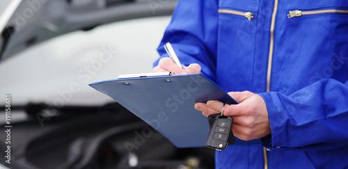 Fotografía  Mechaniker bei der Durchsicht eines Autos, TÜV-Untersuchung