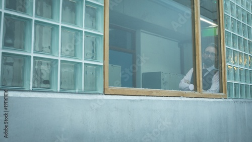 Executive looking through window in office