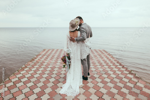 Photo  rear view of bride and groom in boho style hugging on pier at lake