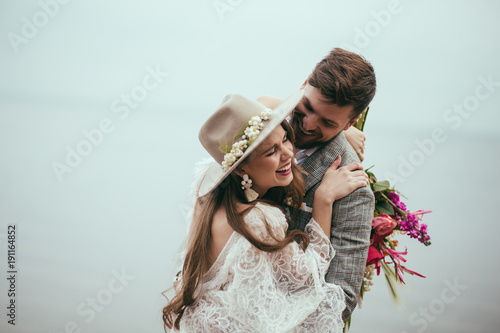 beautiful happy bride and groom in boho style laughing at lake