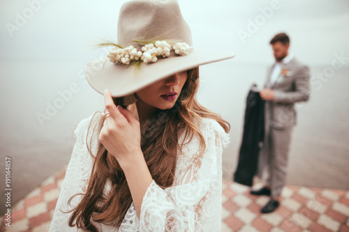 beautiful bride in wedding dress and hat in boho style on pier at lake, groom standing behind