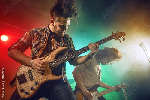 Fotografia Rock band performs on stage. Guitarist, bass guitar and drums.