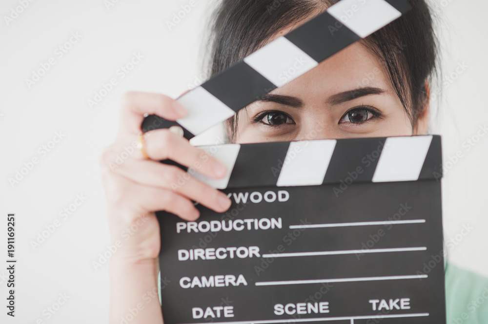 Photo  Young Asian woman playing clapperboard with positive emotion