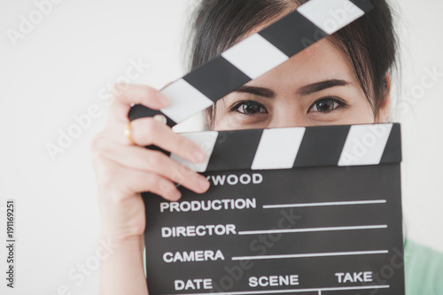 Fototapeta Young Asian woman playing clapperboard with positive emotion