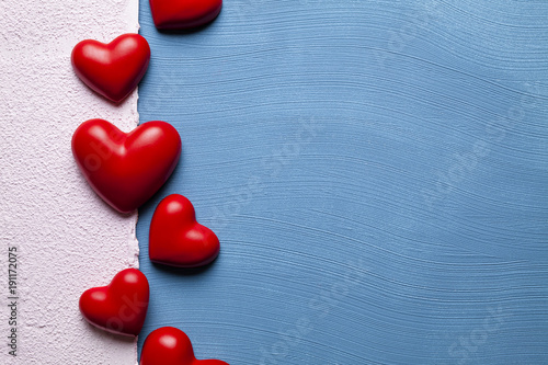 Fotomural Red hearts on blue and pink plastered background