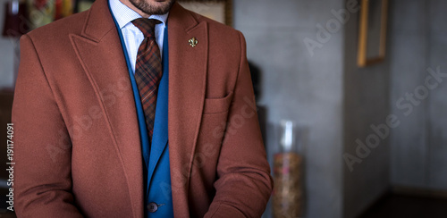 Fotografia Man in custom tailored suit and trench coat posing indoors